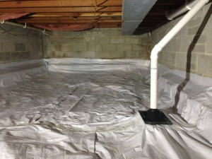 A crawlspace with a poly barrier and radon mitigation pipe.