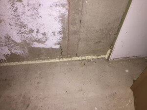 A gap in a basement concrete floor sealed with spray foam, as part of a radon mitigation system.